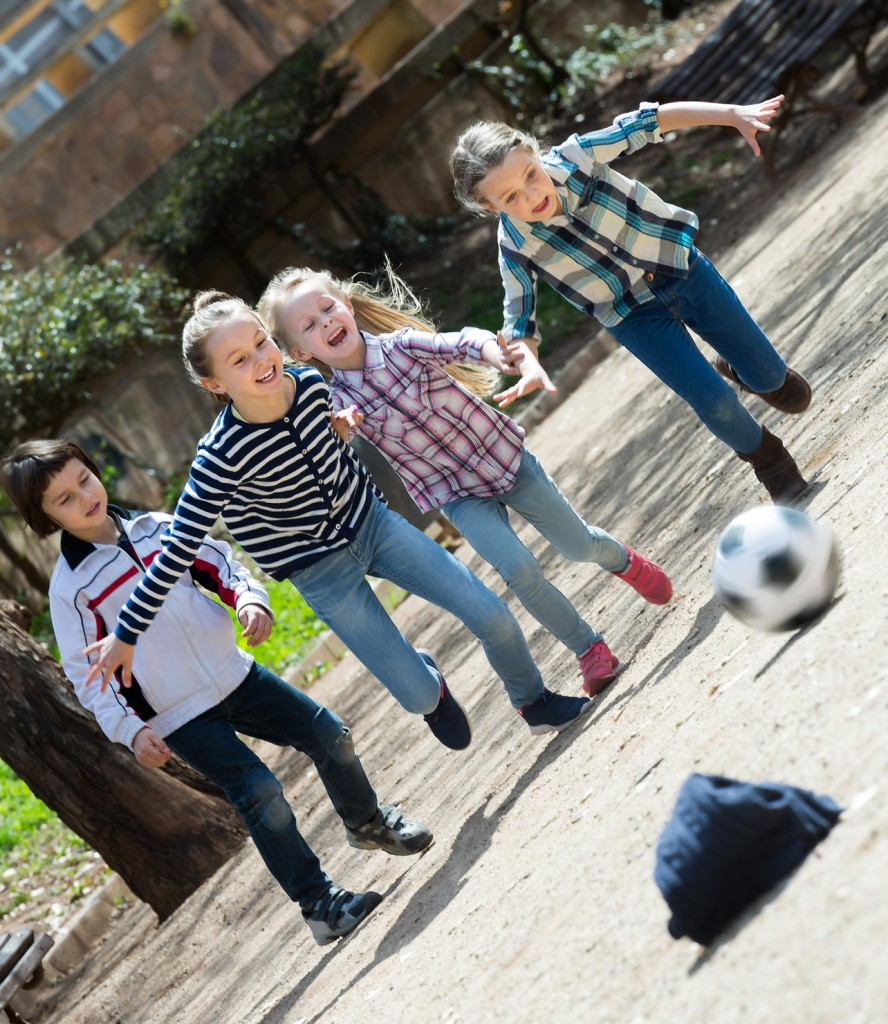 Kids playing street football outdoors in spring day