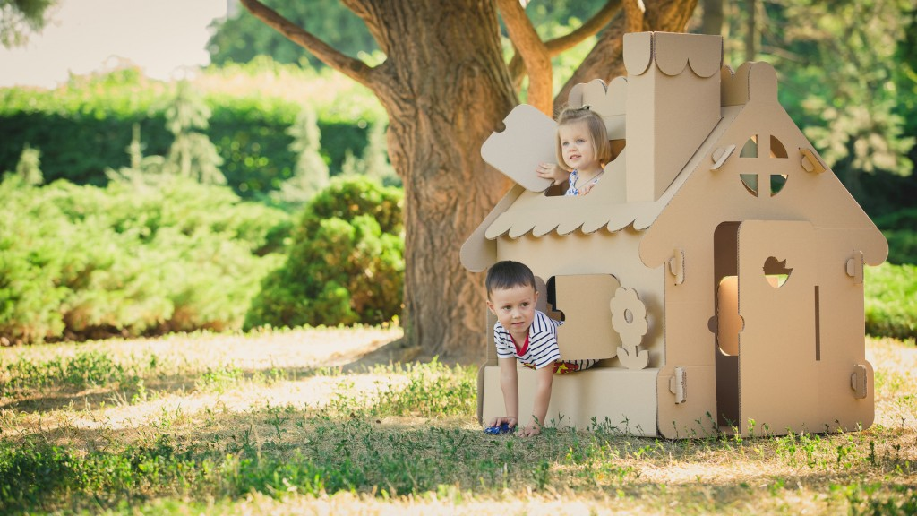 Two funny kids are playing in a cardboard toy house. In a summer day in the park